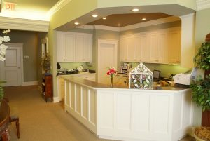 Reception area of Dr. Taylor's facility, with sage green walls, white cabinets, and a white check-in desk.