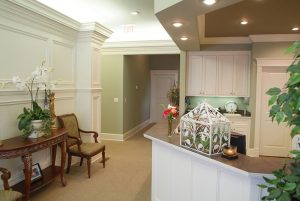 Entryway into Dr. Taylor's facility, which has sage green walls, white cabinets, and a check-in desk.