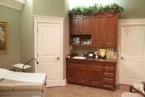Examination room at Dr. Chris Taylor's office, with sage green walls, white doors, and greenery sitting on top of large dark wood cabinets evoking a calming feeling.