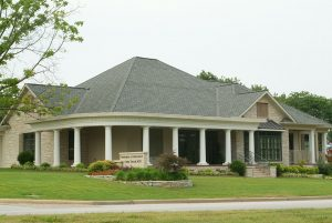 View of the outside of Dr. Taylor's facility, which has a light stone exterior and tall white columns.